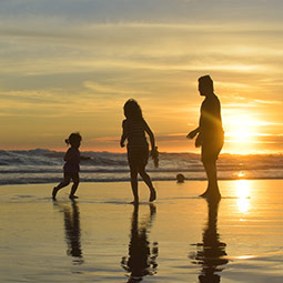 Family enjoying beach at sunset